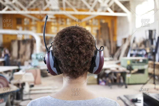 Close up view from behind of a woman factory worker wearing hearing protection in a woodworking factory