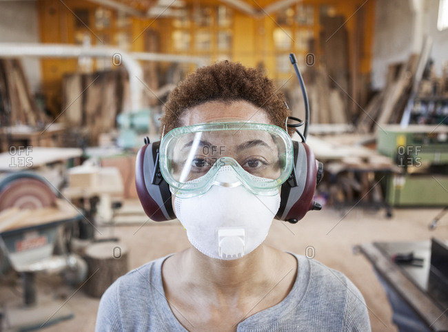 Close up view of black woman factory worker wearing safety glasses and dust nose mask in a woodworking factory