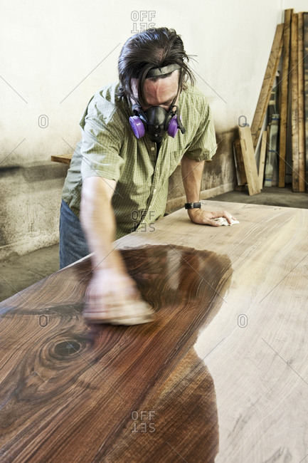 Caucasian man factory worker applying finish to a recycled wood table top in a woodworking factory