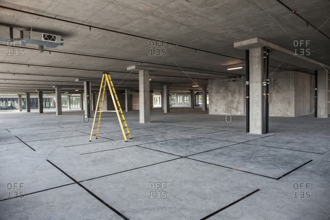 Large empty raw office space with a ladder set up on the floor