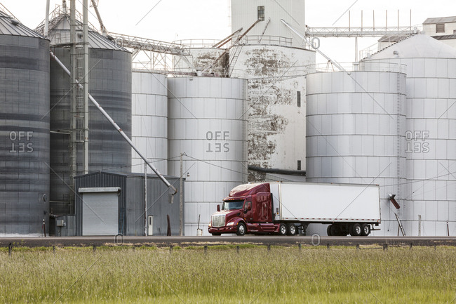 A commercial truck driving past grain elevators in the farm country of eastern Washington, USA