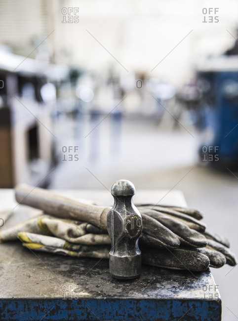 Closeup still life of gloves and a heavy duty hammer in a sheet metal factory