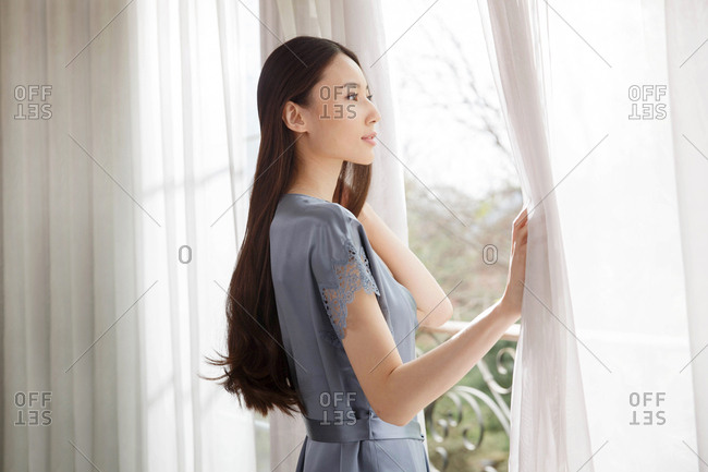 Young woman draws the curtain and looks out