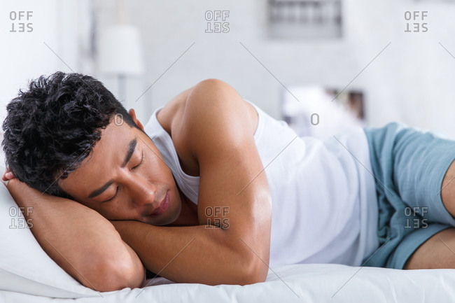 Young man sleeps in his bedroom