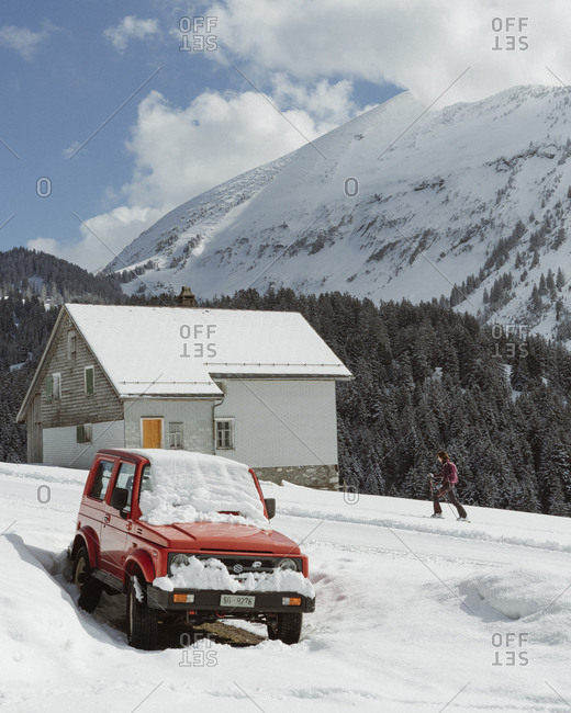 Switzerland - March 14, 2018: Woman skiing past old Suzuki 4x4 car parked in front of Swiss alpine hut with mountains in the background