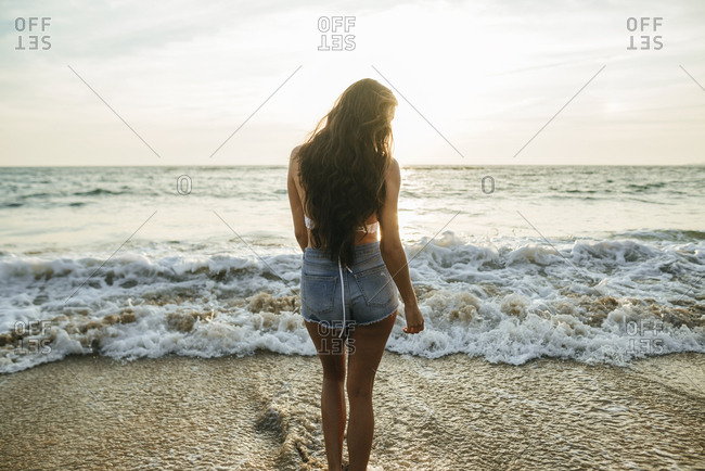 Backside view of woman looking towards the sea