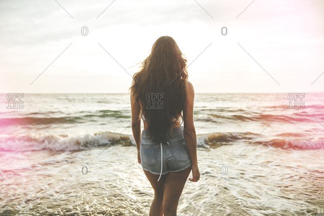 Back view of brunette model watching ocean sunset on the shoreline
