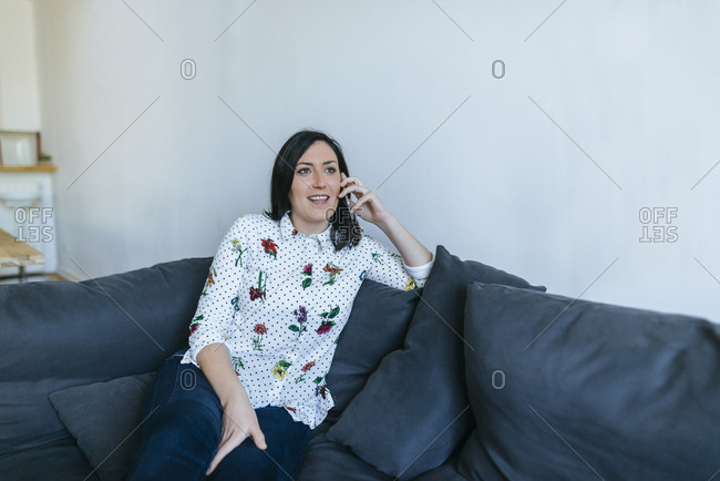 Woman talking on mobile phone on the couch