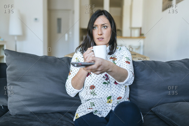 Woman changing channels from the couch