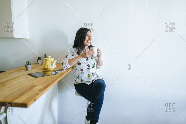 Woman with mug laughing at something off camera