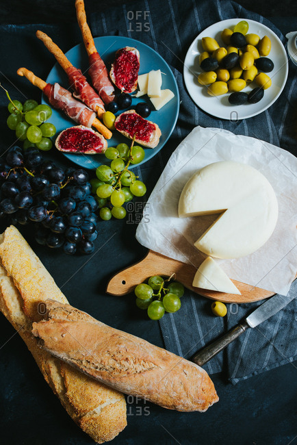 Overhead shot of round cheese on a wooden board next to olives ham grapes and bread