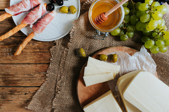 Overhead shot of round hard cheese on a wooden plate next to grapes honey olives and ham