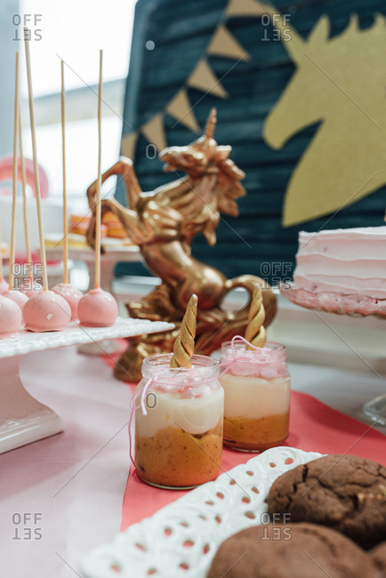 Unicorn themed sweet table with all kind of desserts and a golden unicorn sculpture