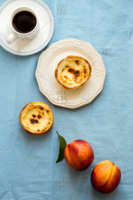 Breakfast with traditional portuguese dessert pasteis de belem, nectarines and black coffee served on blue linen tablecloth