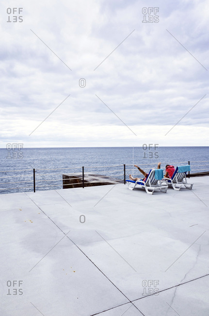Funchal, Portugal - December 7, 2017: Two tourists are relaxing in loungers at the Vidamar Resort Hotel