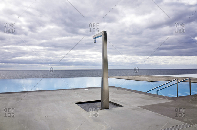 Abandoned swimming pool area with a minimalistic shower