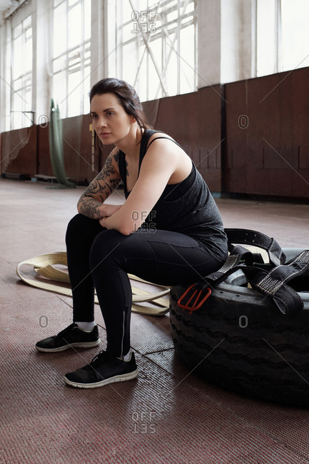 Young tattooed Caucasian woman sitting on tire in gym and looking into the distance