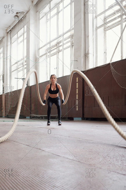 Young slim Caucasian woman in black sportswear burning calories by doing exercise with ropes in gym