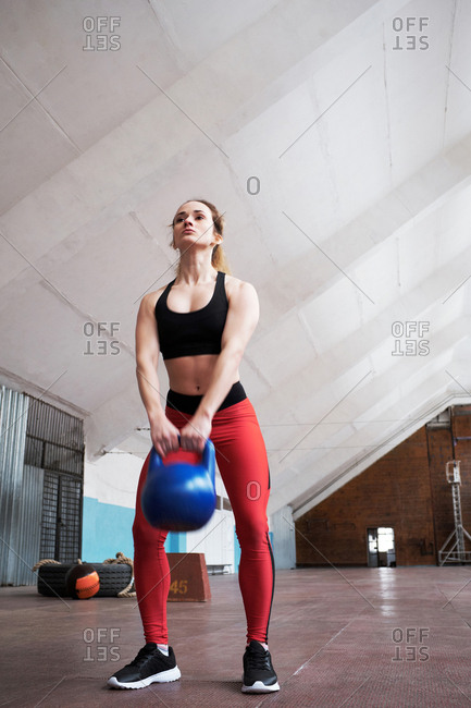 Low angle view of young Caucasian female athlete in sportswear doing exercises with kettlebell in old gym