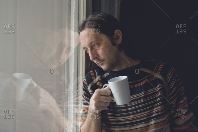 Sad man by window drinking coffee