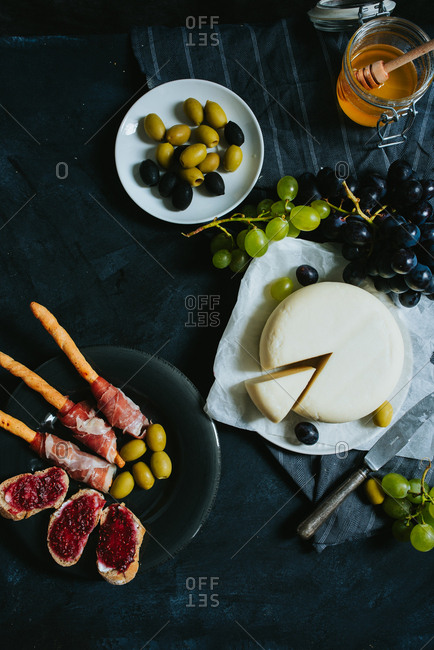 Round cheese on a wooden board next to olives ham grapes and bread