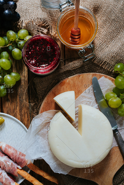 Round hard cheese on a wooden plate next to grapes honey olives and ham