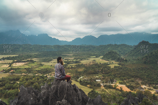 Laos- Vang Vieng- hiker sitting on rock- looking at distance