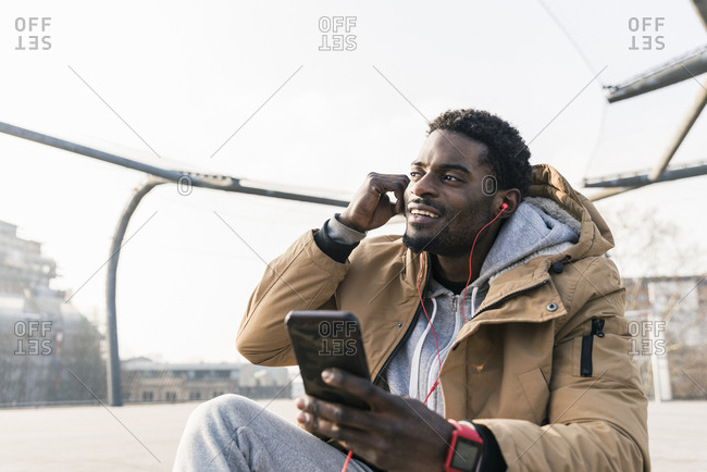Smiling young man with smartphone and earphones outdoors
