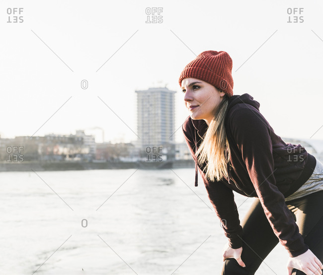 Sportive young woman having a break at the riverside in the city