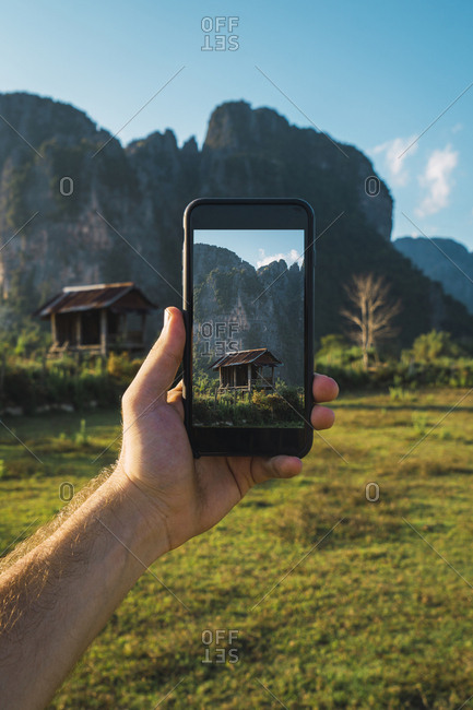 Laos- hand holding smartphone- Display with wooden hut and mountains