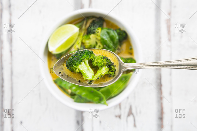 Green thai curry with broccoli- pak choi- snow peas- baby spinach- lime- broccoli and sauce on spoon