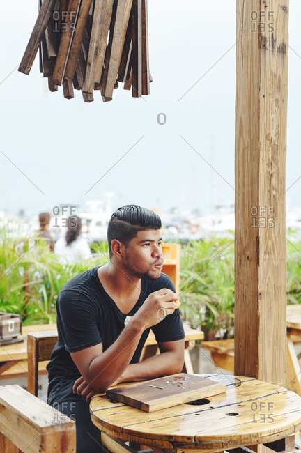 Portrait of young Latin man chewing hamburger at beach restaurant in Santa Marta, Colombia