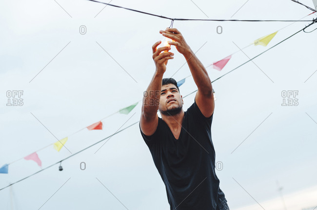 Young Latin man screwing in a light bulb at a beach party
