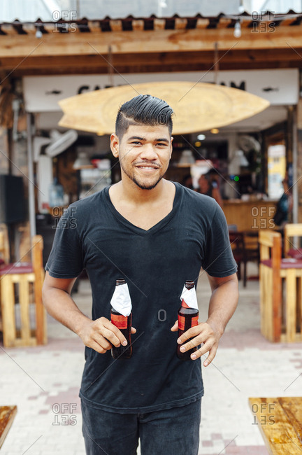 Portrait of young Latin man holding two beer bottles at beach restaurant, Santa Marta, Colombia