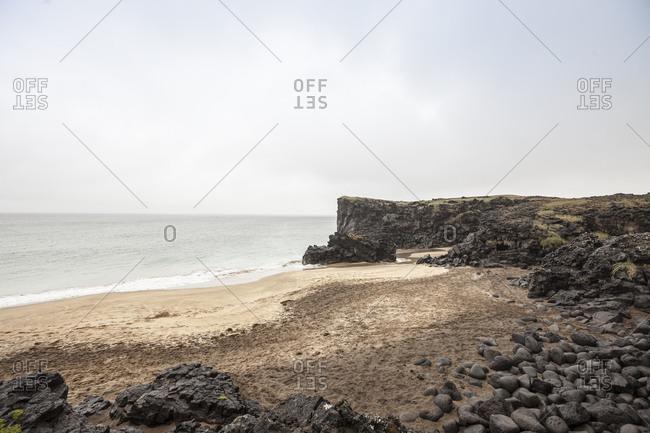 Golden sand beach and tranquil sea at Skardsvik, Iceland