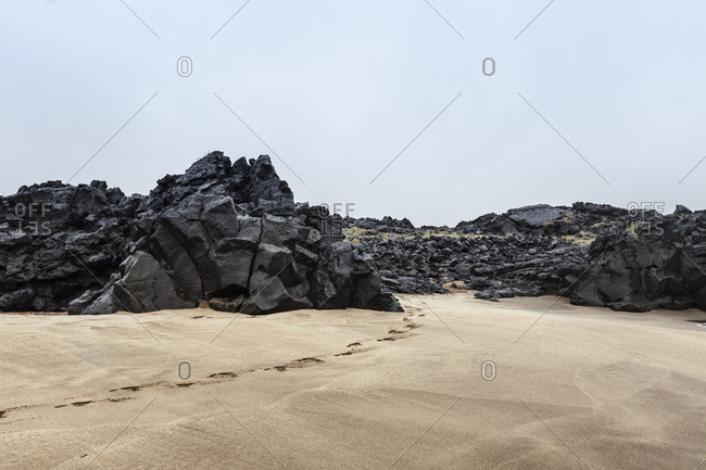 Footprints leading through the rocky basalt gates off the beach at Skardsvik, Iceland
