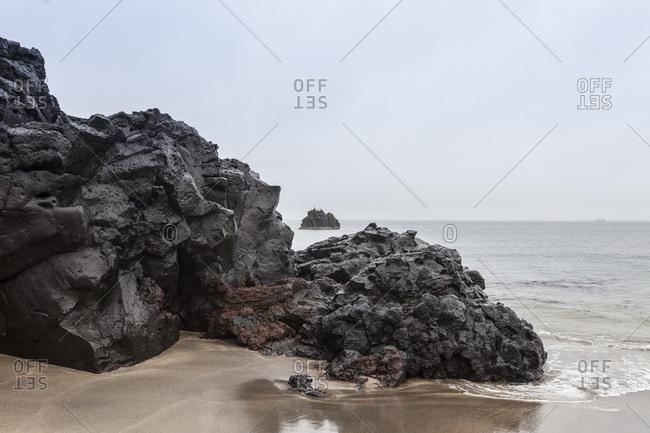 Basalt rock outcrop leading into the sea at Skardsvik, Iceland