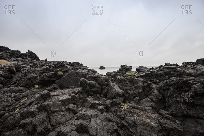 Looking over basalt rock to outcrop in the sea at Skardsvik, Iceland