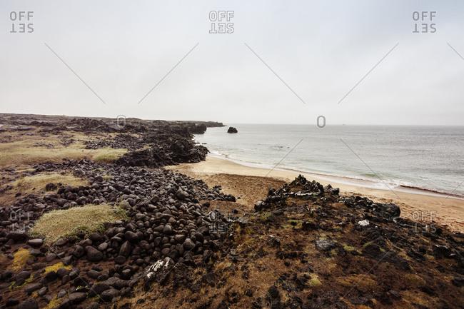 Weathered rocks and golden sands on the coast at Skardsvik, Iceland
