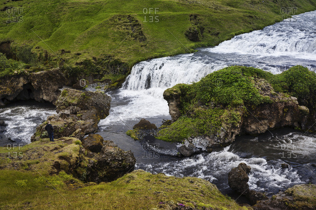 Looking down on tourist standing on river bank looking at Skoga waterfalls in southern Iceland