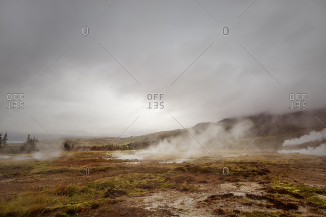 Steam rising from the ground in the Haukadalur geothermal area in Iceland
