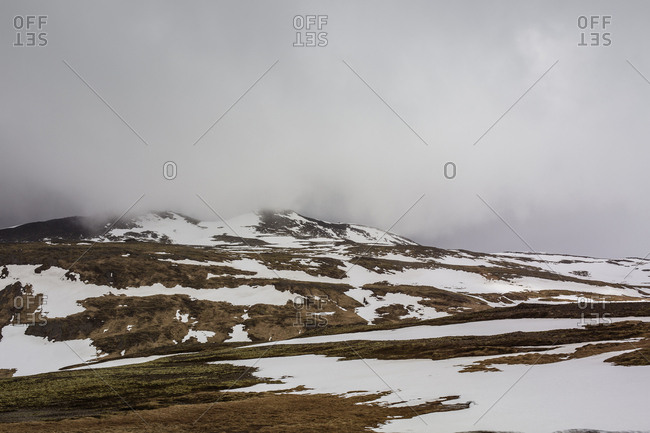Looking up snowy hill to peak shrouded in low cloud