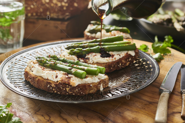 Pouring balsamic vinegar over asparagus and ricotta cheese toast