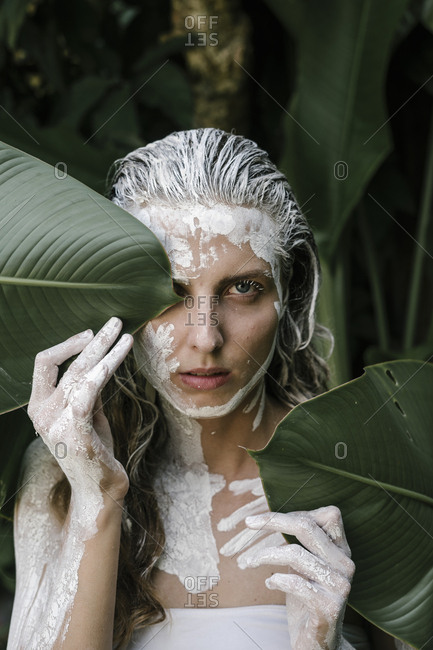 Woman with white paint on her body hiding behind leaves