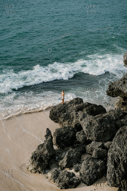 Bird's eye view of woman standing on rocks on a beach in Bali