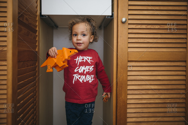 Young boy playing with toys inside an empty wooden closet