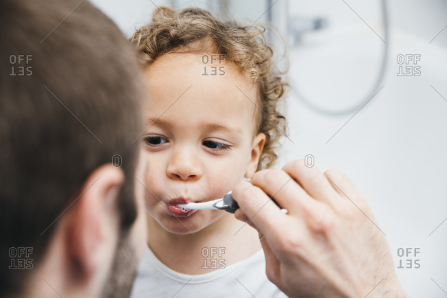Father brushing his son's teeth in bathroom