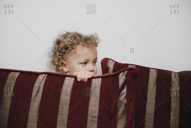 Young boy hiding behind sofa cushions