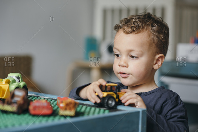 Young kid playing with his toy cars