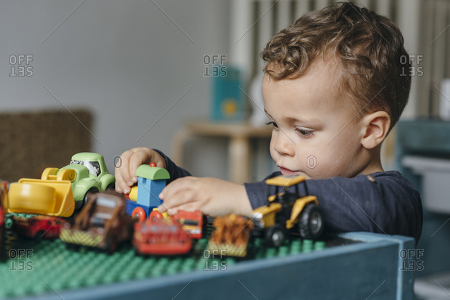 Boy playing with wooden train and toy cars on his desk